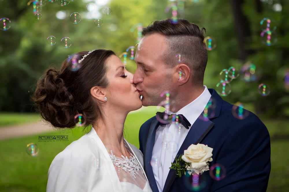 Hochzeit in Dessau, Brautpaar küsst sich inmitten von Seifenblasen