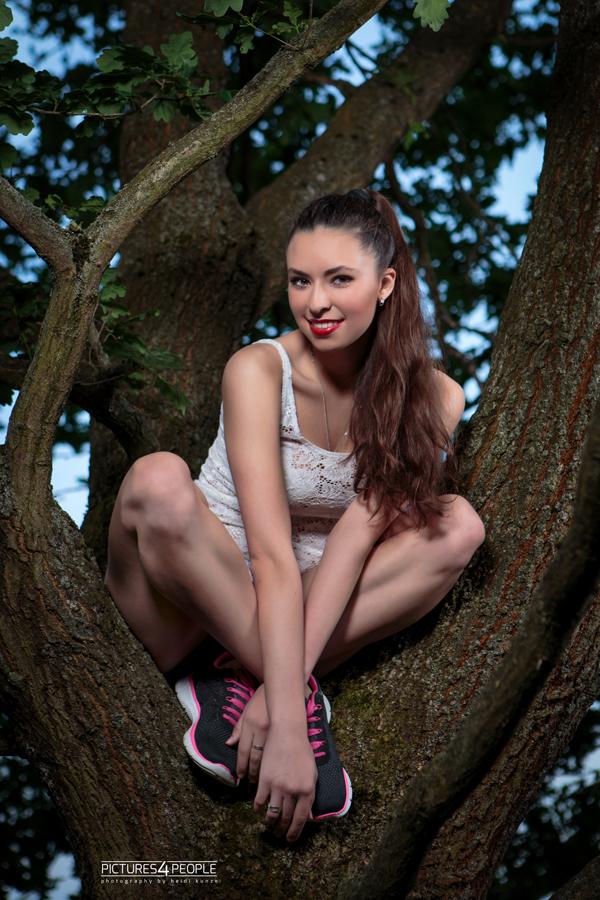 Mädchen hockt im Baum