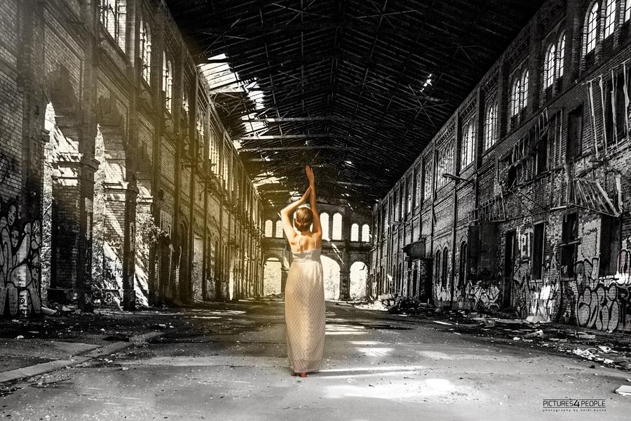 Mädchen in Fabrikhalle, ein Sonnenstrahl trifft sie