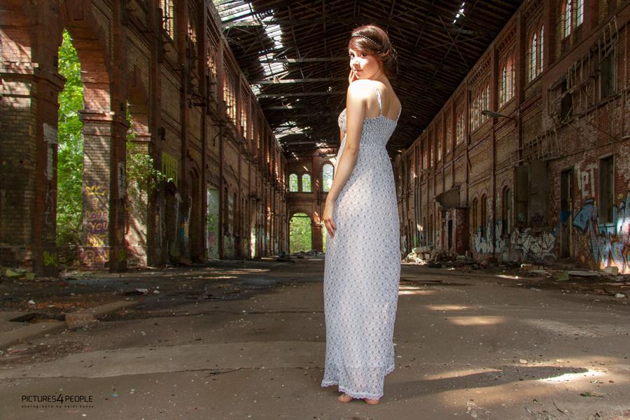 Mädchen in Fabrikhalle, sie steht mit dem Rücken zum beobachter, dreht sich aber gerade um