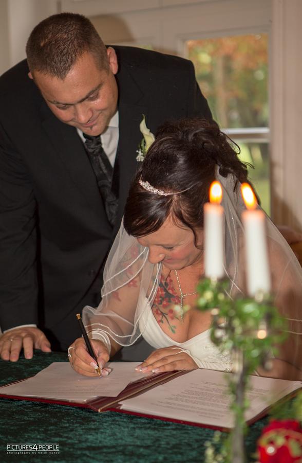 Braut unterzeichnet Papiere zur Hochzeit