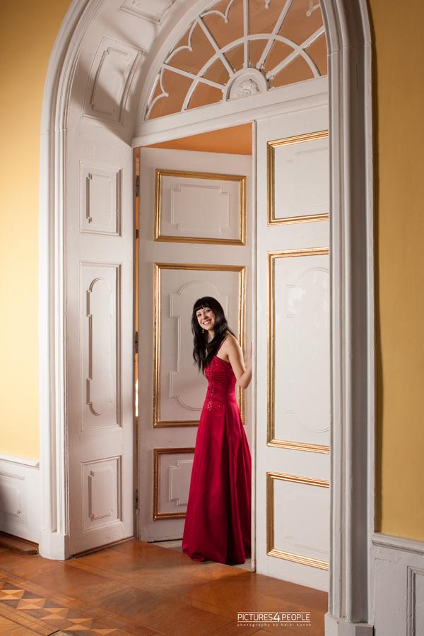 junge Frau öffnet eine Tür in einem Schloss