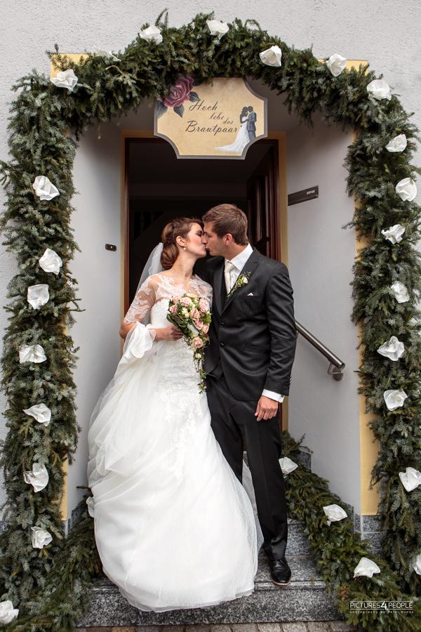 Brautpaar vor der geschmückten Haustür
