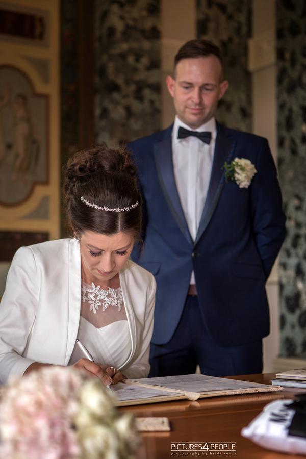 Hochzeitspaar im Dessauer Luisium beim unterschreiben der Papiere