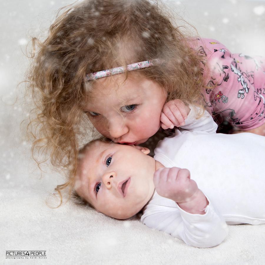große Schwester küsst kleine Schwester, fotografiert von Familienfotografin aus Dessau