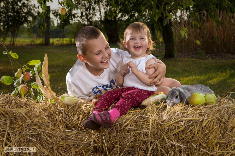 Geschwister auf Strohballen im Spätsommer mit Kaninchen, fotografiert von Familienfotografin aus Dessau