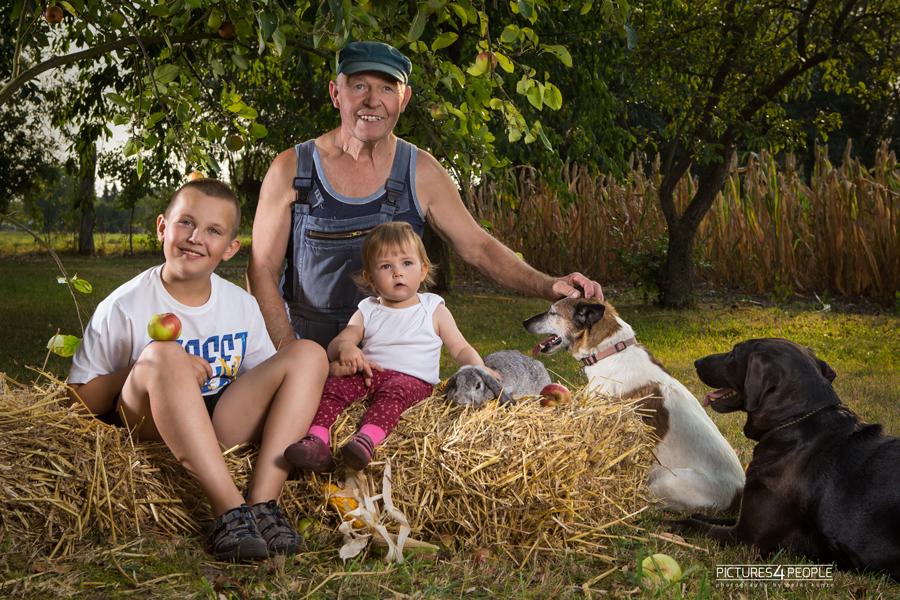Geschwister mit dem Opa auf Strohballen im Spätsommer mit Kaninchen, fotografiert von Familienfotografin aus Dessau