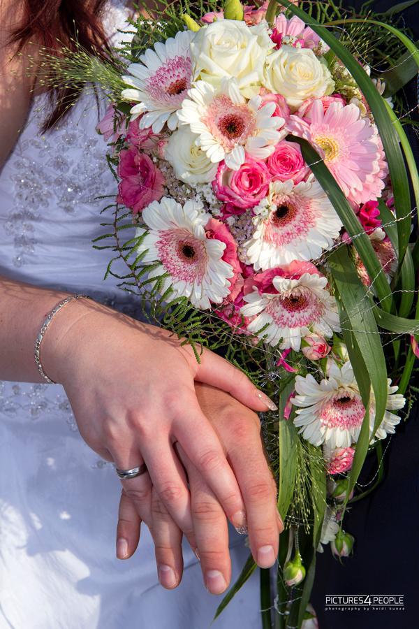 Hände des Brautpaares vor dem Brautstrauß