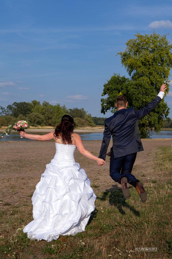 springendes Hochzeitspaar vor der Elbe in Dessau, fotografiert von Hochzeitsfotografin aus Dessau