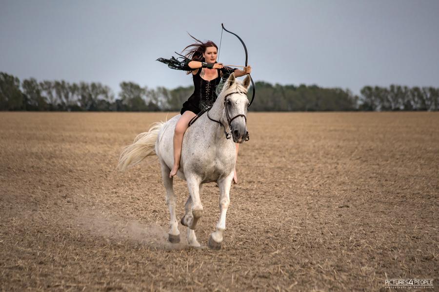 Reiterin ohne Sattel mit Bogen auf einem Stoppelfeld