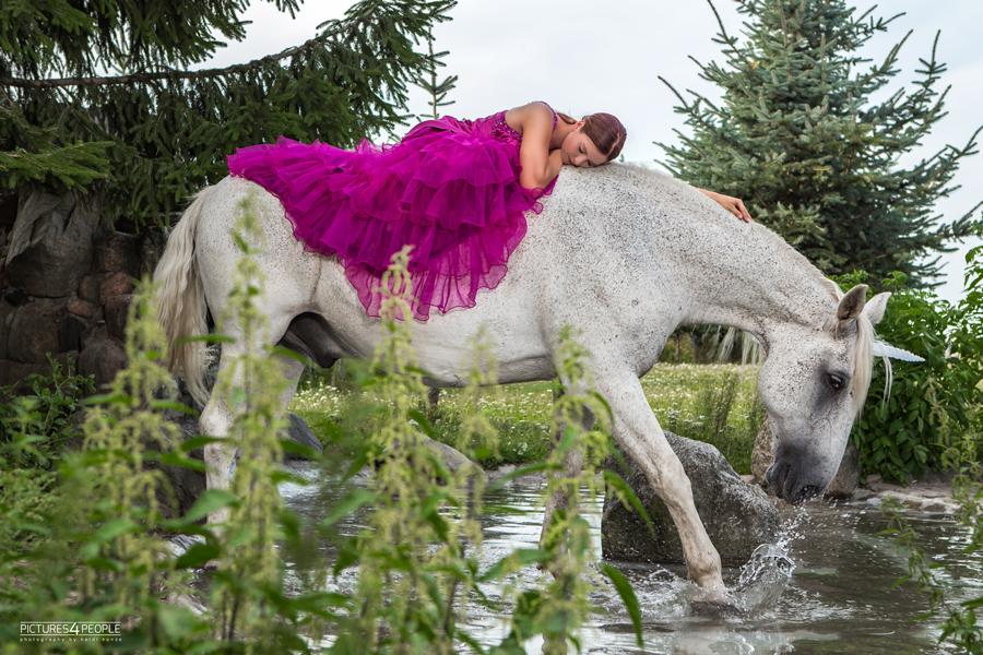 junge Frau liegt auf einem Pferd