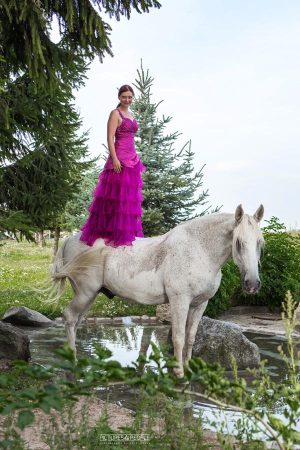 junge Frau steht auf einem Pferd
