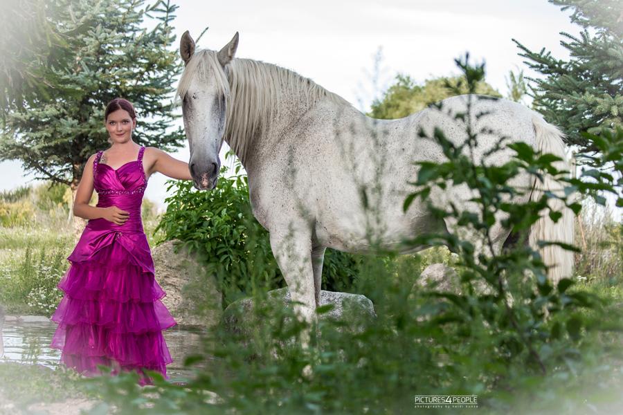 junge Frau steht neben ihrem Pferd