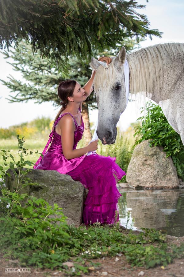 junge Frau sitzt neben ihrem Pferd