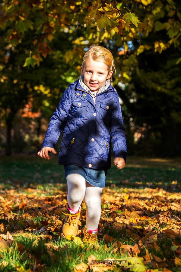 kleines Mädchen rennt im Laub