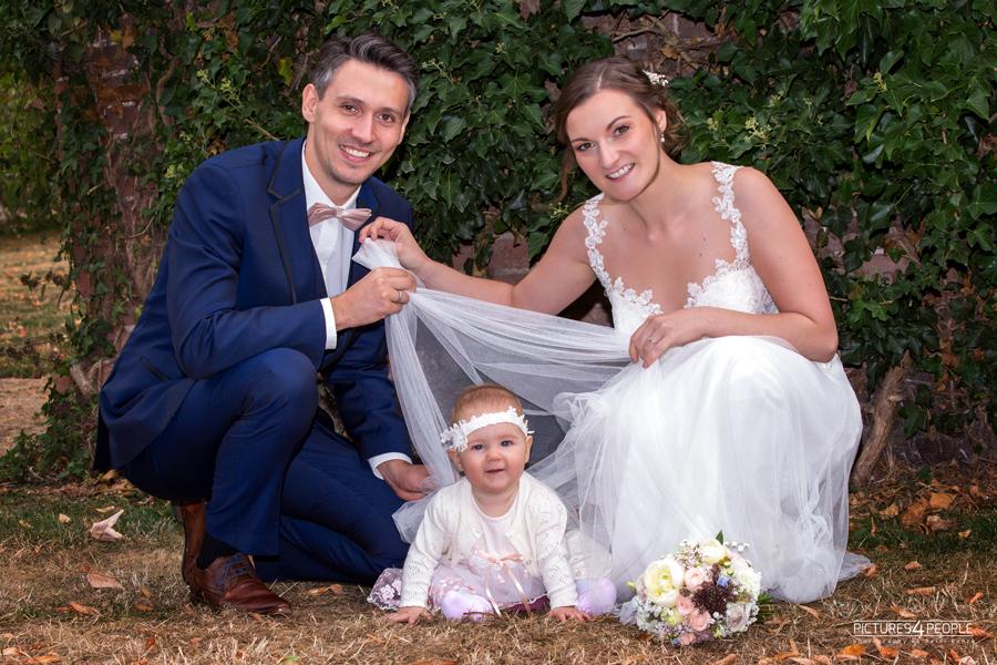 Hochzeitspaar mit Baby im Garten, fotografiert von Hochzeitsfotograf aus Dessau