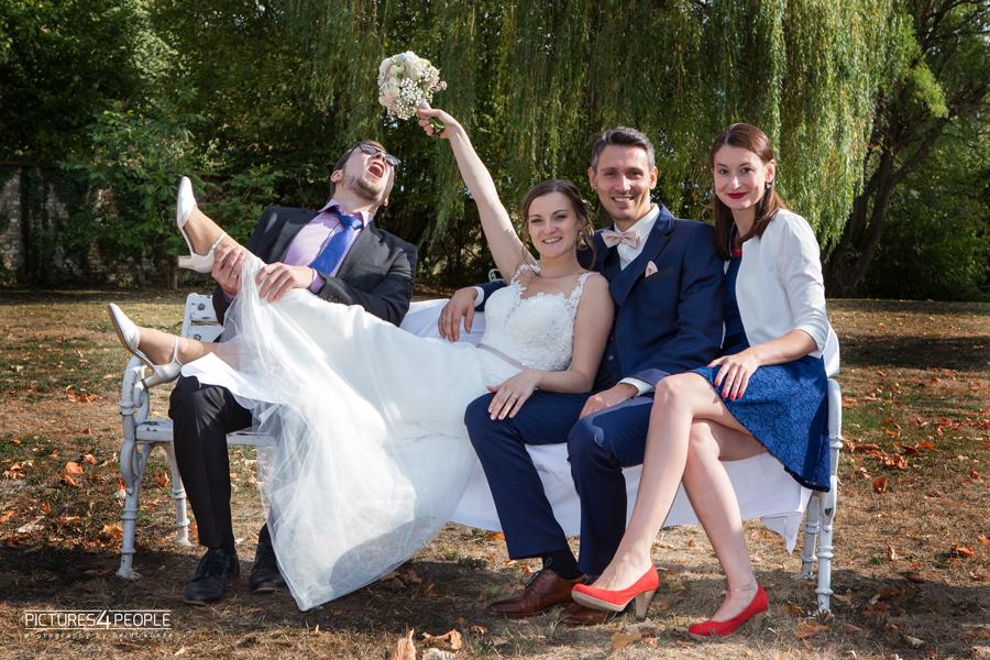 Brautpaar mit Freunden auf einer Bank, festgehalten von Hochzeitsfotograf Dessau