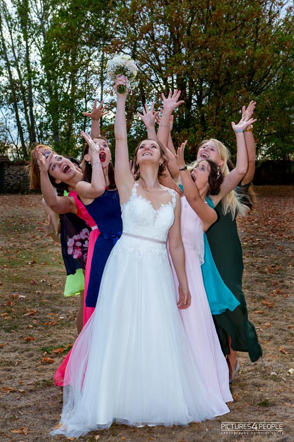 Braut wirft den Brautstrauß, hinter ihr stehen die Freundinnen, fotografiert von Hochzeitsfotograf Dessau