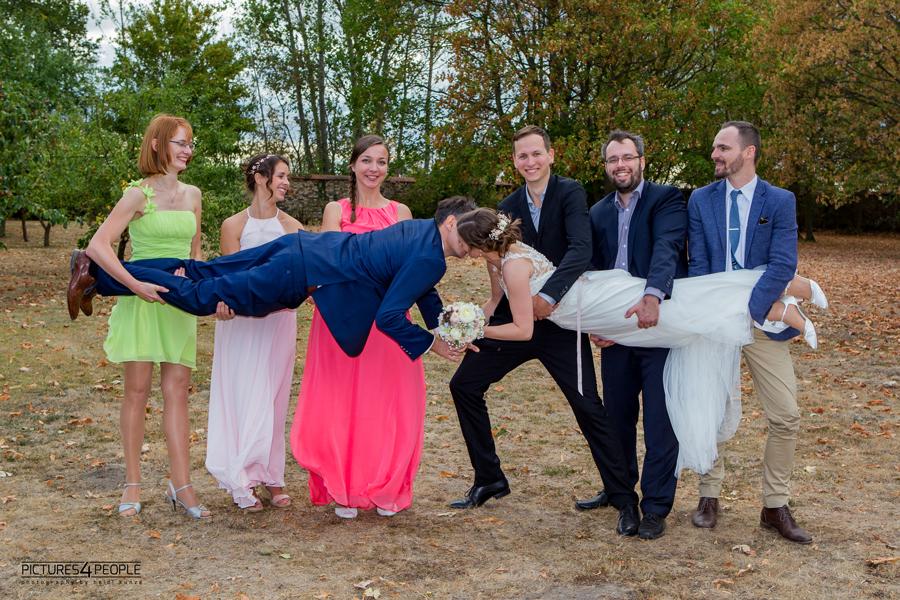 Brautpaar wird von Freunden gehalten, sie küssen sich, fotografiert von Hochzeitsfotograf Dessau
