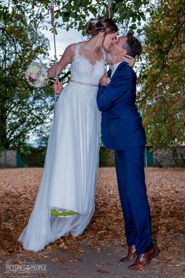 küssendes Brautpaar, sie steht auf einer Kinderschaukel in Zörbig, fotografiert von Hochzeitsfotograf Dessau