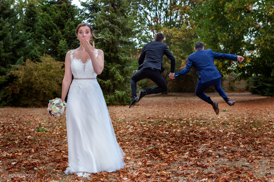 erschrockene Braut, Bräutigam läuft im Hintergrund mit einem Mann weg, fotografiert (im Spaß) durch Hochzeitsfotograf Dessau
