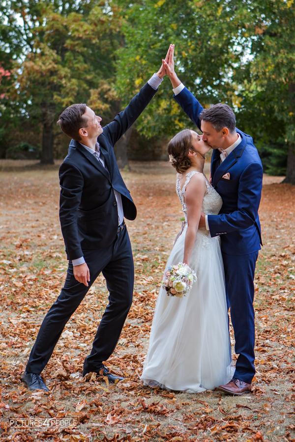 Bräutigam klatscht sich mit einem Freund ab, er küsst dabei die Braut, fotografiert von Hochzeitsfotograf Dessau