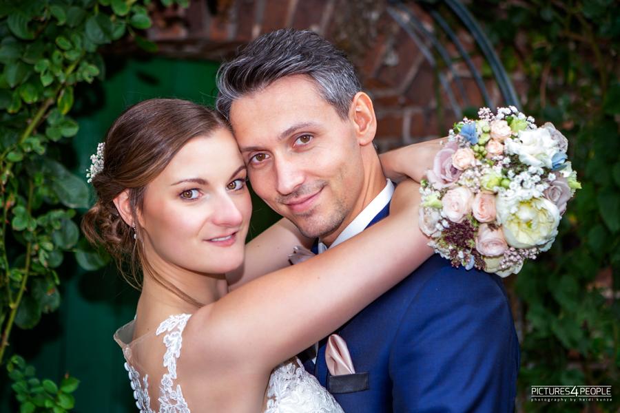 Brautleute mit Strauß, kuschelnd, fotografiert von Hochzeit Fotograf aus Dessau, Zörbig, Wittenberg, Köthen, Bernburg, Roßlau, Bitterfeld, Delitzsch, Halle, Leipzig