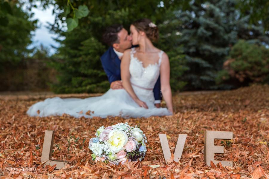 küssendes Brautpaar im trockenen Laub in Zörbig, Schriftzug LOVE im Vordergrund, fotografiert von Hochzeitsfotograf aus Dessau, Zerbst, Aken