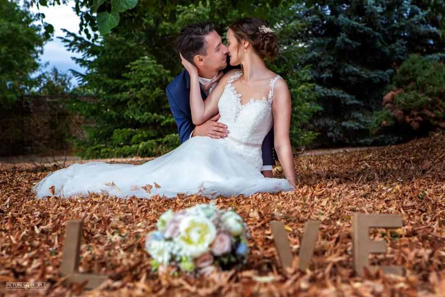 küssendes Brautpaar im trockenen Laub in Zörbig, Schriftzug LOVE im Vordergrund, fotografiert von Hochzeit Fotograf aus Dessau, Wittenberg, Coswig, Bitterfeld, Aken, Bernburg, Zerbst