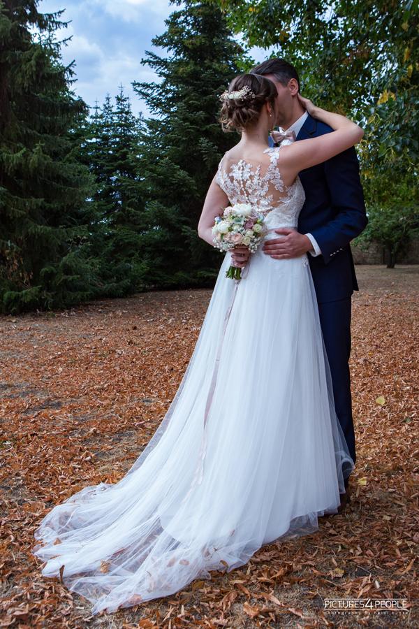 küssendes Brautpaar im trockenen Laub in Zörbig, die Braut steht mit dem Rücken zum Beobachter, fotografiert von Hochzeitsfotograf aus Dessau, Wittenberg, Coswig, Bitterfeld, Aken, Bernburg, Zerbst