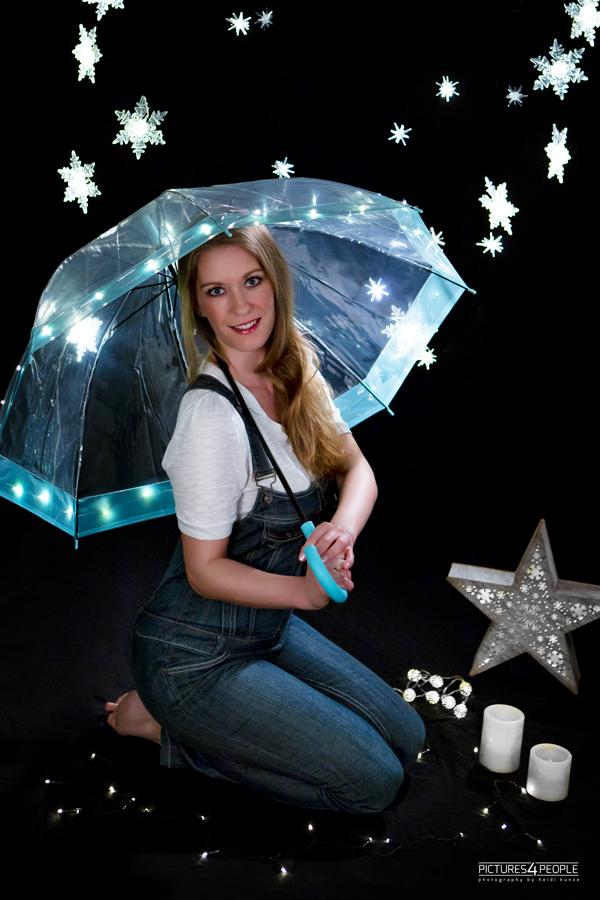 junge Frau unter einem Regenschirm, mit Lichterketten