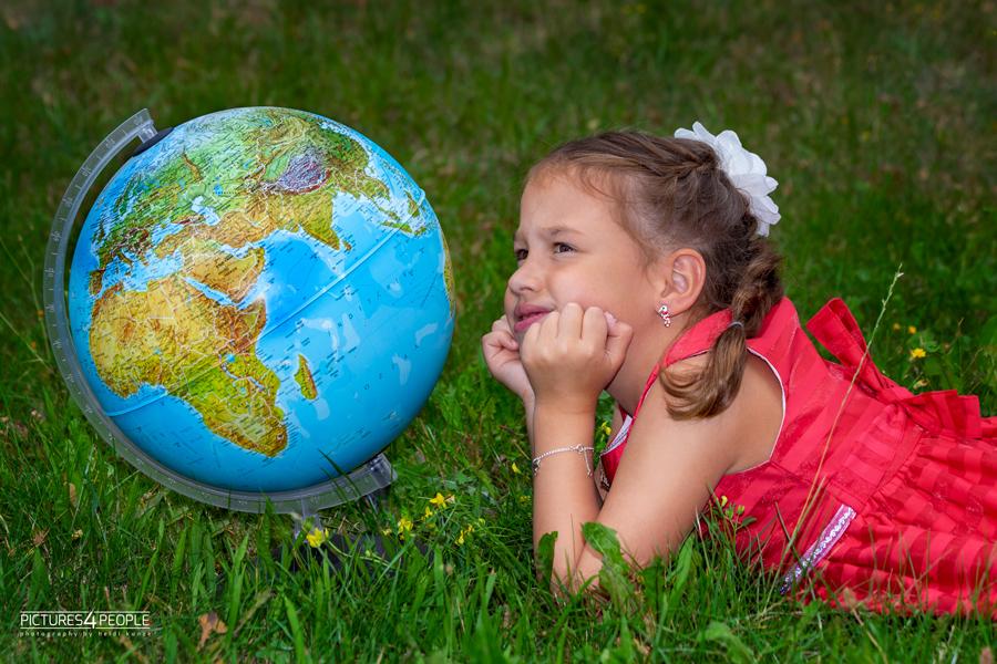 Einschulung, Kind neben Globus und schaut fragend in den Himmel