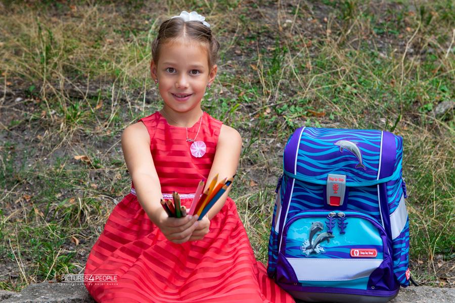 Einschulung, Kind mit vielen Buntstiften und Ranzen