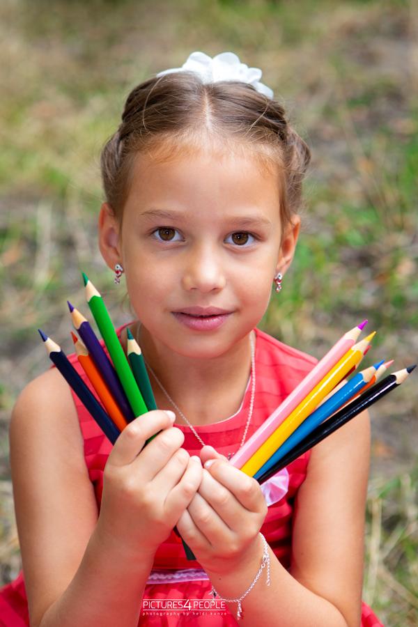 Einschulung, Kind mit vielen Buntstiften