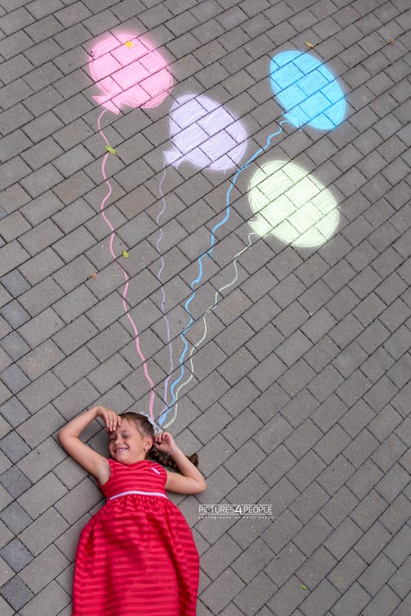 Einschulung, Kind liegt auf dem Pflaster, Luftballons sind neben ihr gemalt