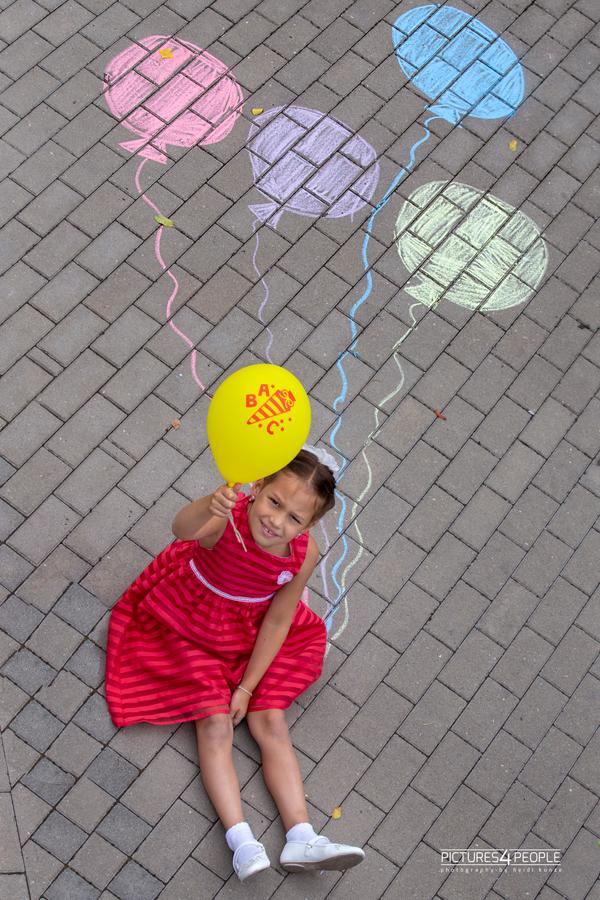 Einschulung, Kind sitzt auf dem Pflaster, Luftballons sind neben ihr gemalt