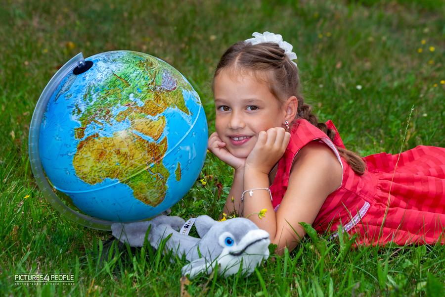 Einschulung, Kind liegt im Gras neben einem Globus