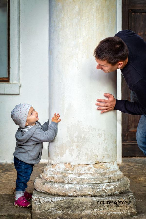 Papa mit kleiner Tochter an einer Säule
