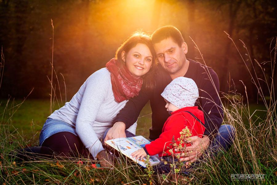 Familie mit Kleinkind im herbstlichen Wald vor untergehender Sonne