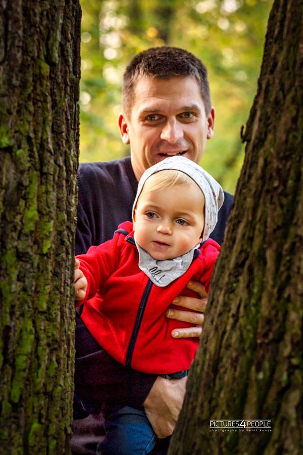 Papa mit Kleinkind an einem Baum