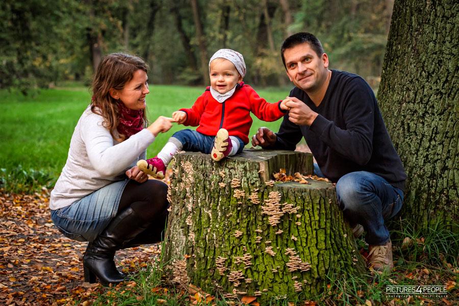 Kleinfamilie im herbstlcihen Wald auf Baumstumpf