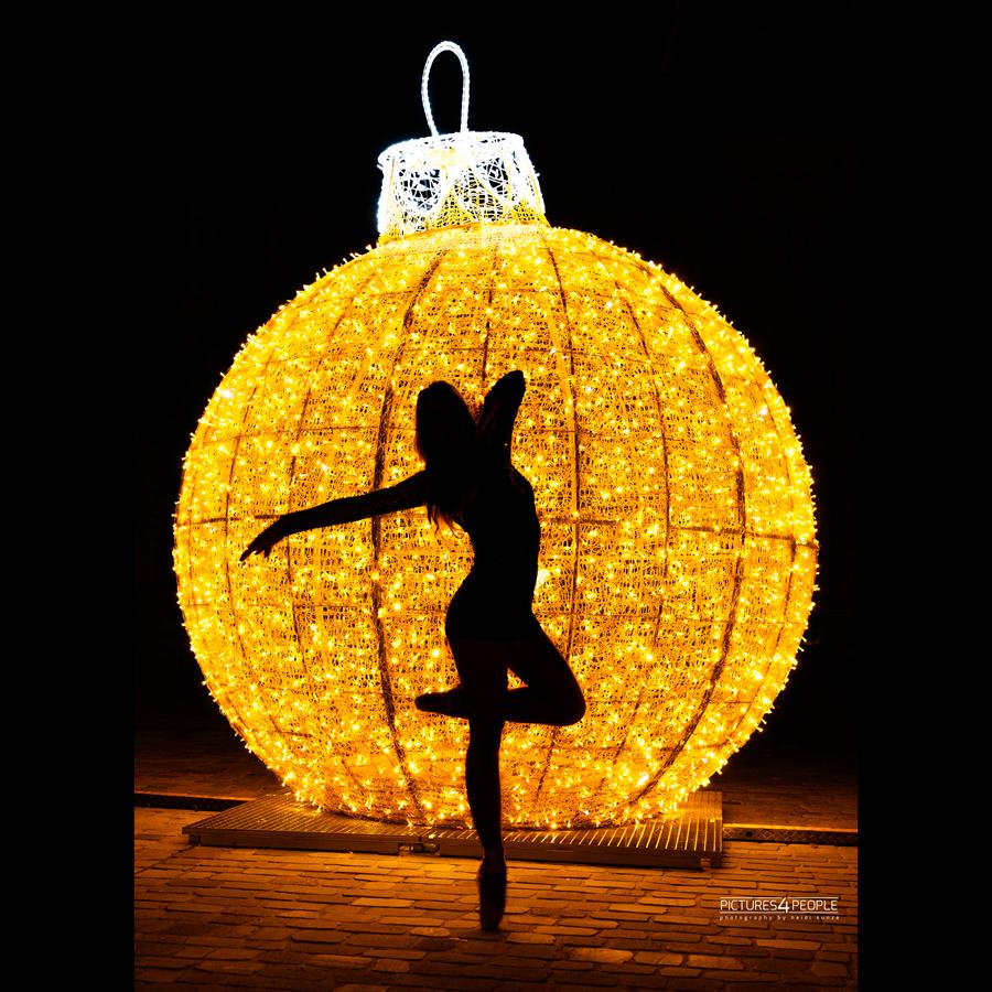 Lichterwelt Magdeburg, Tänzerin als Silhouette vor einer glänzenden goldenen Kugel