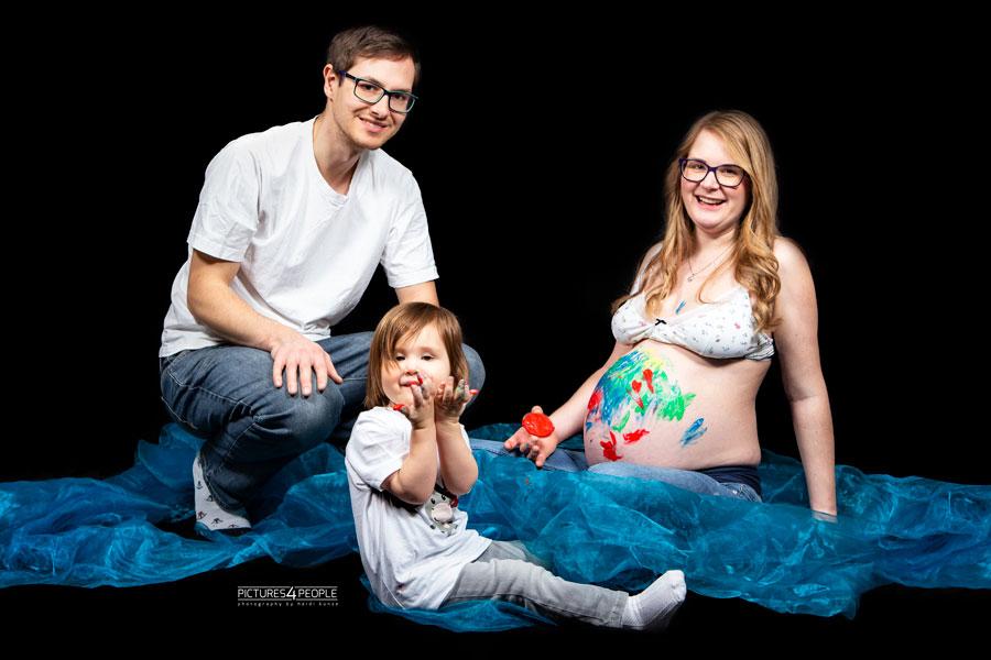 Homeshooting, Kleinkind bemalt Babybauch der Mama mit Fingerfarben