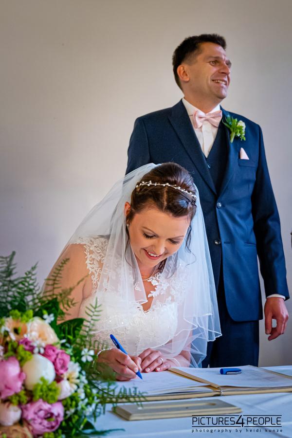 Hochzeit, Braut unterschreibt Eheurkunde