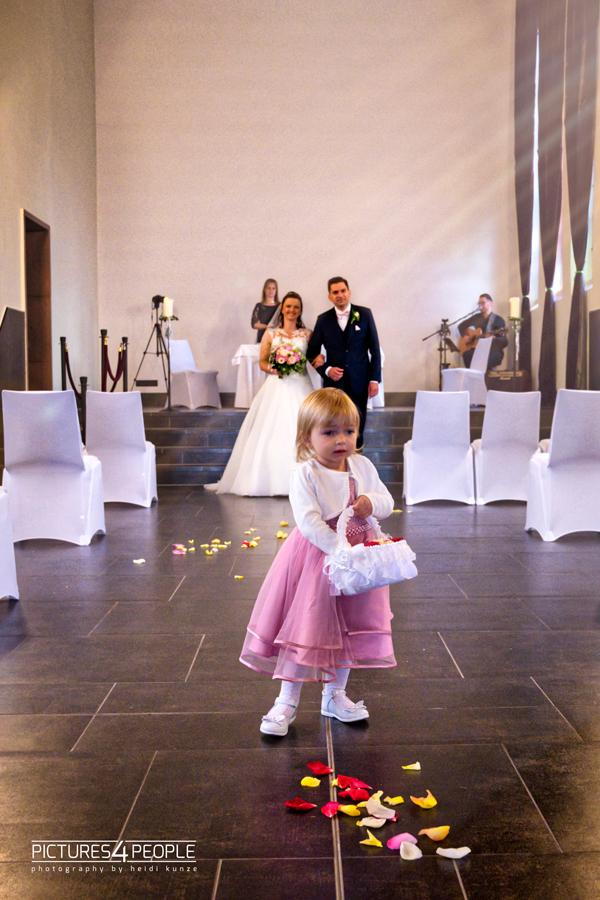 Hochzeit, kleines Mädchen streut Blütenblätter vor dem Brautpaar