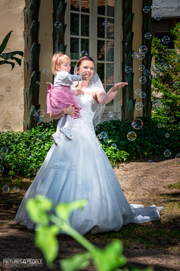 Hochzeit, Braut hat Tochter auf dem Arm, beide bestaunen Seifenblasen