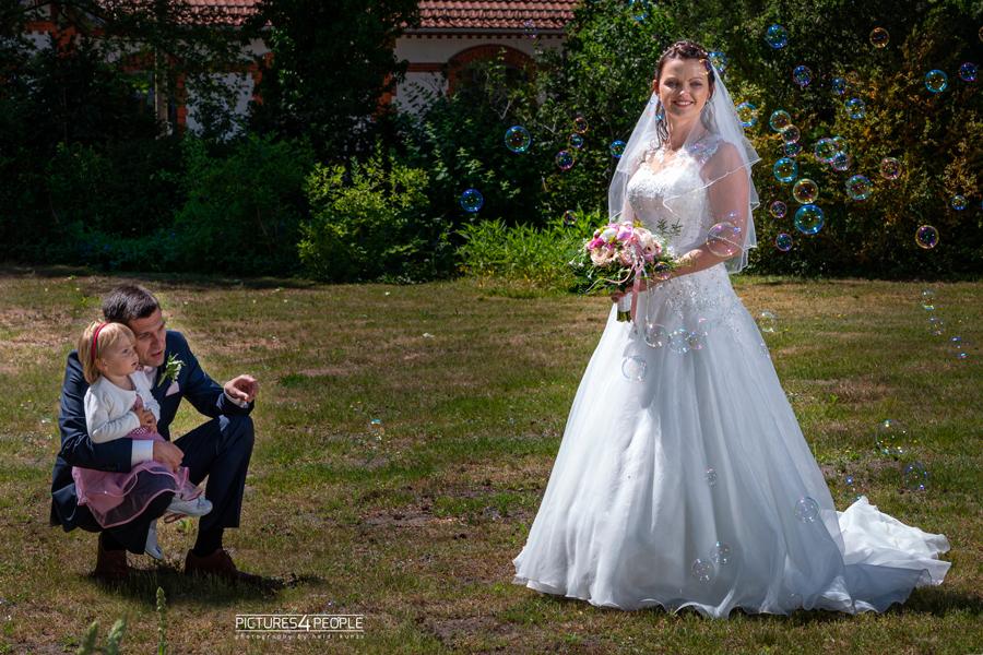 Hochzeit, Tochter sitzt auf Papa's Schoß, Braut steht daneben
