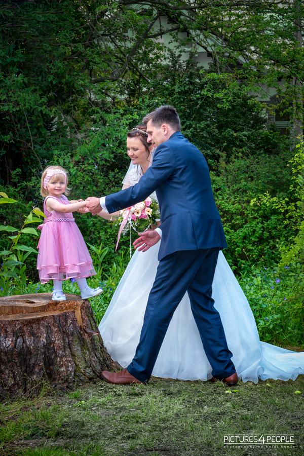Hochzeit, Tochter steht auf einem Baumstumpf, Eltern helfen beim Herunterspringen