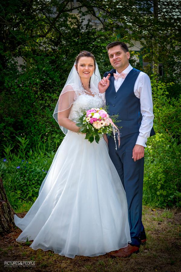 Hochzeit, Paar steht entspannt im Grünen