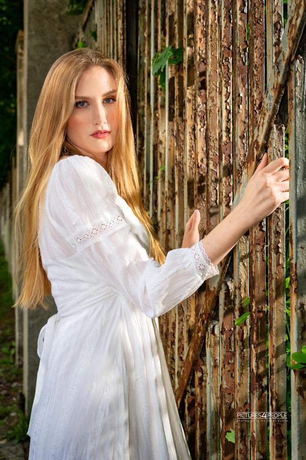 Fotograf aus Dessau; junge Frau an einem alten Zaun